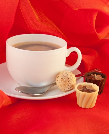 Cup of coffee with chocolates on red silk photo