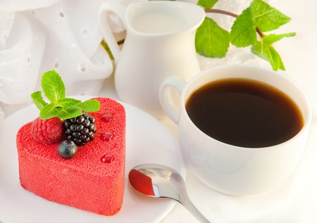 Cake in the form of heart with a blackberry, a raspberry and mint, a cup of coffee photo