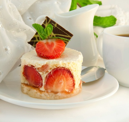Cake from cream and a strawberry with mint, a cup of coffee photo