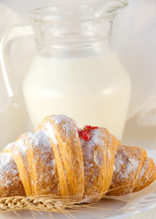 Croissant with jam and a milk jug, a light morning meal photo