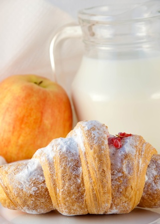 Croissant with jam and a jug of milk and an apple, a light morning meal photo