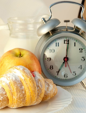Croissant with jam and a jug of milk and an alarm clock, a light morning meal Stock Photo - 11188373