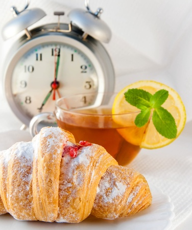Croissant with jam and tea with a lemon and an alarm clock, a light morning meal Stock Photo - 11188377
