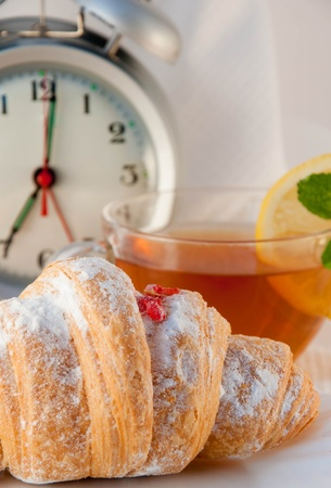 Croissant with jam and tea with a lemon and an alarm clock, a light morning meal photo