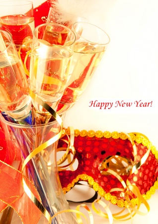 Christmas card. Glasses with champagne and a New Years mask, a carnival photo