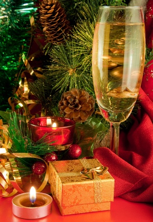 Christmas card. Champagne, a branch of a fur-tree and a candle on a red background