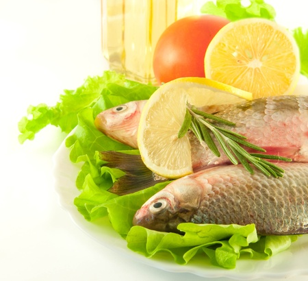 Fresh fish, crucian with a lemon and an onions, salad with olive oil Stock Photo - 11377077
