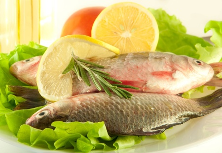Fresh fish, crucian with a lemon and an onions, salad with olive oil photo