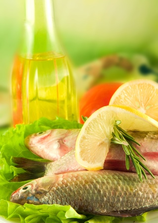 Fresh fish, crucian with a lemon and an onions, salad with olive oil Stock Photo - 11377051