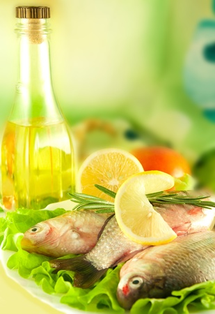 Fresh fish, crucian with a lemon and an onions, salad with olive oil Stock Photo - 11377041