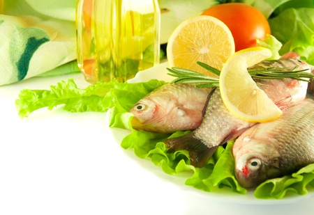 Fresh fish, crucian with a lemon and an onions, salad with olive oil Stock Photo - 11377049