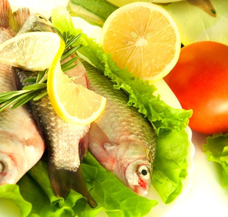 Fresh fish, crucian with a lemon and an onions, salad with olive oil Stock Photo - 11377055