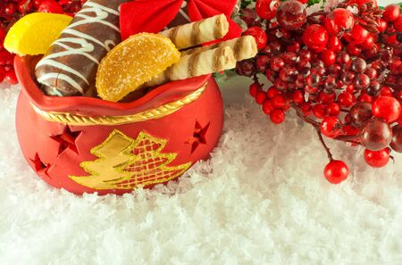 Christmas bag with gifts, cookies and fruit candy, a fur-tree branch photo