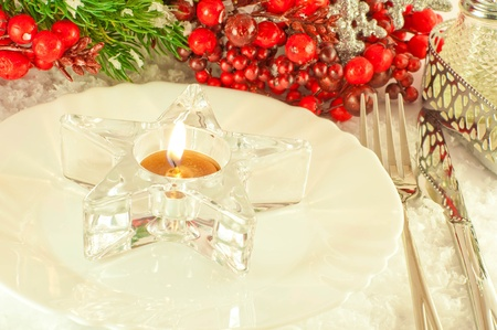 Christmas table layout, candlestick in the form of a star with a branch of berries Stock Photo - 11377115