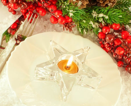 Christmas table layout, candlestick in the form of a star with a branch of berries photo