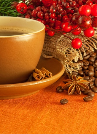 Christmas branch from berries and a fur-tree and a cup of coffee