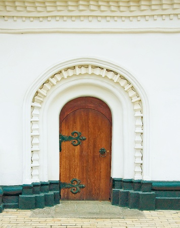 Ancient door in a white wall of a monastery photo