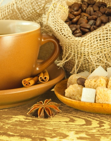 Cup of coffee with chocolates, coffee grains with cinnamon and an anise photo