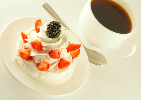 Cake from cream, strawberries and blackberries, a cup of fragrant coffee photo