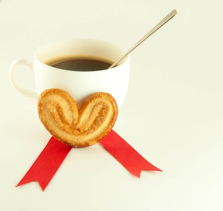 Cake in the form of heart with red ribbon , a cup of coffee photo