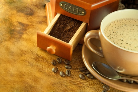 Coffee grinder in a retro style, a cup of coffee on grange background photo