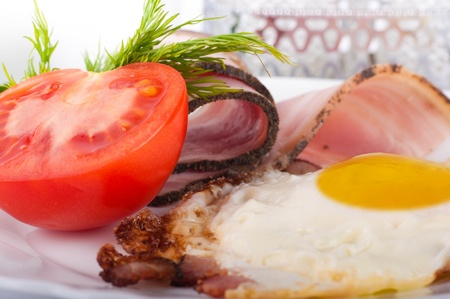 Fried eggs with bacon and tomatoes, a nourishing breakfast photo