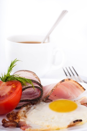 Fried eggs with bacon and tomatoes, a cup of coffee, a nourishing breakfast photo