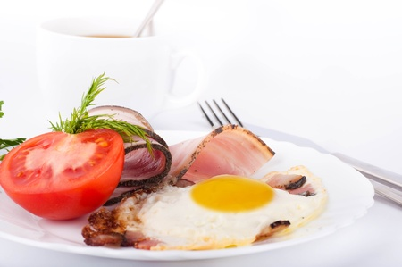 Fried eggs with bacon and tomatoes, a cup of coffee, a nourishing breakfast Stock Photo - 12949288
