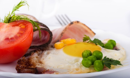 Fried eggs with bacon and tomatoes, a peas and corn, a nourishing breakfast Stock Photo - 12949375