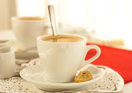 Cup of coffee with fragrant crouton on a red napkin photo