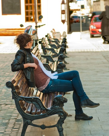 The beautiful young girl sits on a bench in the old city photo