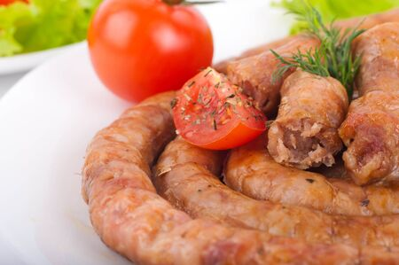 Sausage from pork and beef with tomatoes and spices, vegetable salad photo