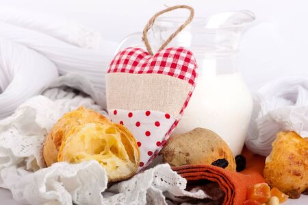 Jug with milk, bread and red heart on a white background photo