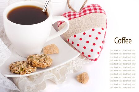Cup of coffee, bread and red heart on a white background photo
