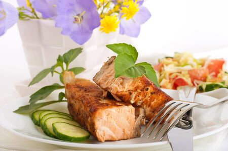 A trout is fried with a pepper and basil, tomatoes and field flowers photo