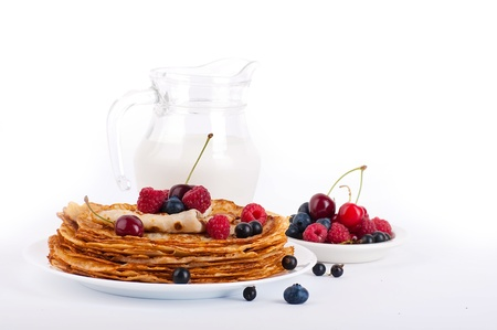 Pancakes with berries and jug of milk photo