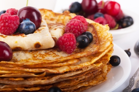 Pancakes with berries on a white background photo