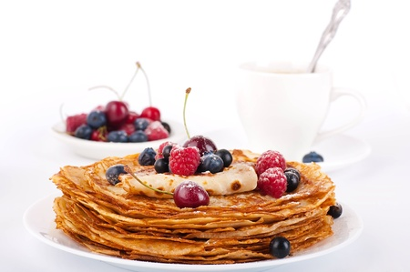 Pancakes with berries and cup of coffee on a white background photo