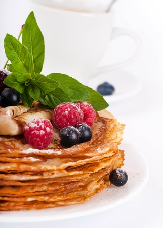 Pancakes with berries and mint on a white background photo
