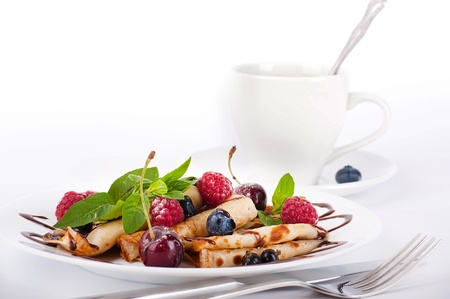 Pancakes with berries and mint and cup of coffee on a white background photo