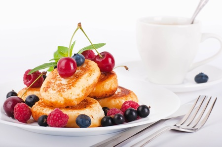 Cheese pancakes with forest berries and cup of coffee photo