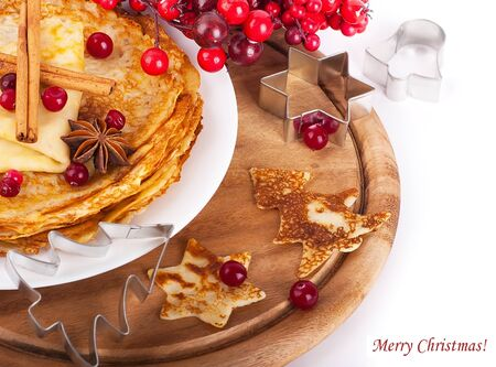 Pancakes with christmas berries and pastry forms of fir-tree and star photo