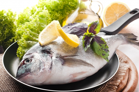 Fresh fish of dorado on a frying pan with a lemon and olive oil photo