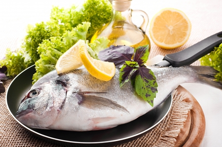 Fresh fish of dorado on a frying pan with a lemon and olive oil Stock Photo - 16311750