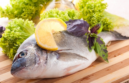 Fresh fish of dorado on a frying pan with a lemon and olive oil Stock Photo - 16311744