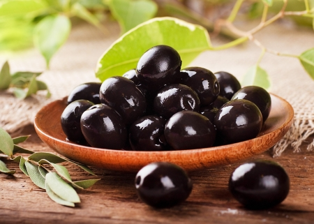 Black olives in a wooden plate and a rough board Stock Photo - 17092317