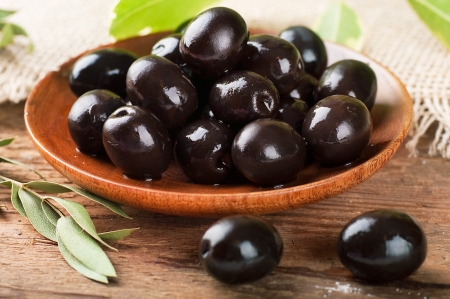 Black olives in a wooden plate and a rough board Stock Photo - 17092353