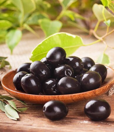 Black olives in a wooden plate and a rough board Stock Photo - 17092314