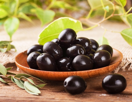 spanish food: Black olives in a wooden plate and a rough board Stock Photo