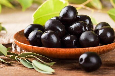 Black olives in a wooden plate and a rough board Stock Photo - 17092336